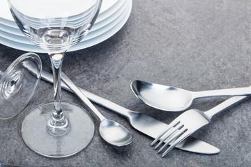 Glänzende Gabel, Teelöffel, Löffel und Messer aus Edelstahl und Gläser angeordnet auf einer schwarzen Granitplatte