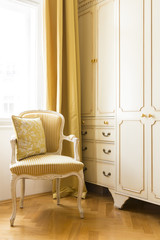 Elegant bedroom sitting area with white painted wood cabinets and chair, parquet floors and silk window draperies