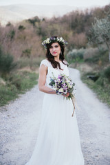 portrait of bohemian bride in nature, with bouquet and crown of