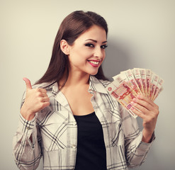 Happy young casual woman in glasses holding roubles and showing