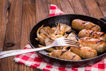 sausage and mushrooms in a frying pan