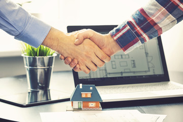real estate agent shaking hands with customer after deal at offi