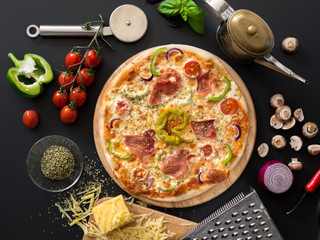 Pizza with tomatoes, cheese, basil and ham on a black background