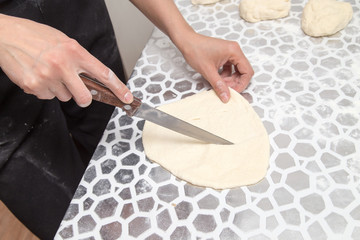 cutting the dough with a knife in the kitchen