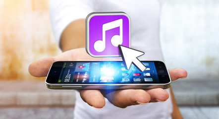 Young man using modern mobile phone to listen music
