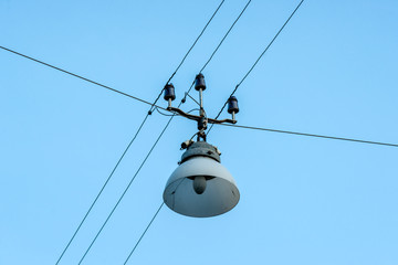 Old street lamp hanging on wires