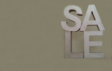 Sale sign. Wording and letters made from a cardboard on paper background.