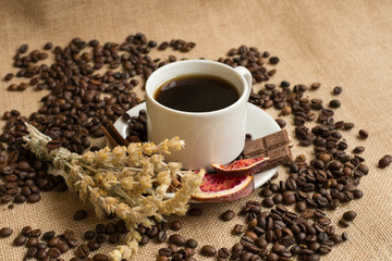 Coffee cup with raw beans on burlap background