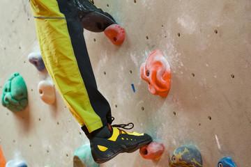 Beine eines jungen Mannes beim Klettern in der Halle