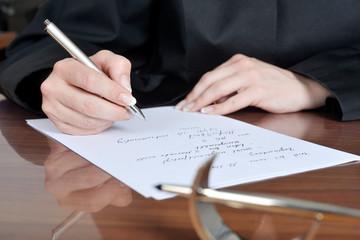 Anwältin macht sich in ihrer Kanzlei Notizen für Prozessauftakt