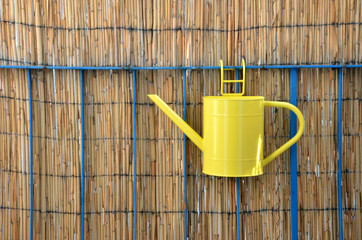 Yellow metal watering can (pot) hang on balcony railing, bamboo fence in background