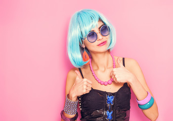 Funny girl portrait smiling and wearing wig with thumbs up