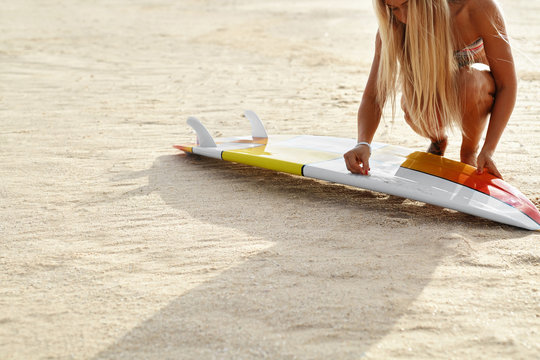 Summer Water Sports. Surfing. Beach Vacation. Beautiful Fit Surfer Woman In Bikini Waxing Surf Board With Wax On Sand Beach. Healthy Active Lifestyle. Leisure Sport. Hobby, Wellness