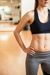 Strong woman with toned abs at a gym