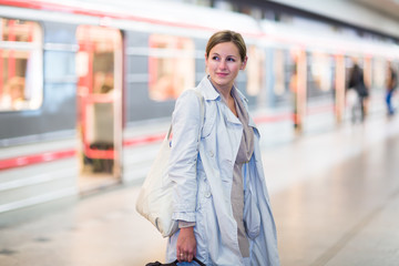 Elegant, smart, young woman taking the metro/subway