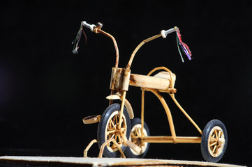 Miniature of wooden kids bicycle on black background. Macro shot.