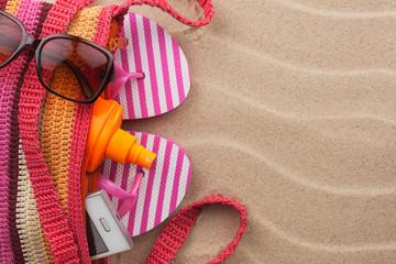 Beach bag with sunscreen, flip flops, cellphone, sunglasses.