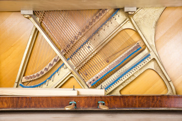 Bottom structure of an upright piano: pedals, metal frame with strings, bass and treble bridges.