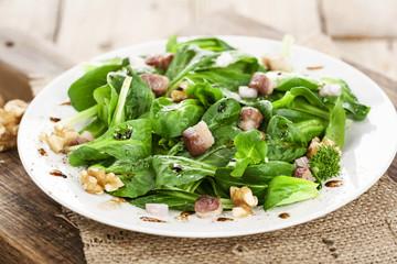 Feldsalat angemacht mit Speckwürfeln und Walnüssen