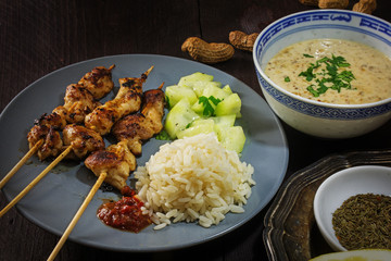 Asian satay meat skewers with rice, cucumber salad and peanut satay
