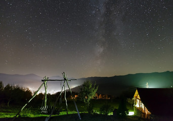 Starry night sky over mountain village.