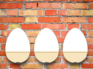 Close-up of three hanged blank Easter egg frames with clips against orange brick wall background