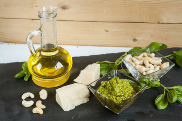 Basil pesto fresh basil leaves parmigiano cheese olive oil and cashew seeds on black stone background