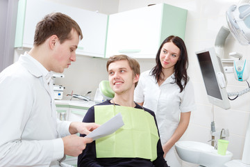 Cheerful young dentist is examining teeth of young man. He is holding patient card.  The female assistant is halping