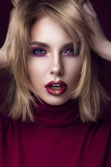 Beautiful blonde woman in a red sweater with bright makeup and dark lips. Beauty face.