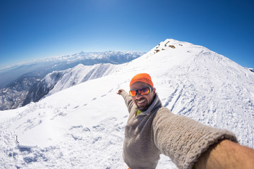 Alpinist taking selfie on snowcapped mountain, fisheye lens