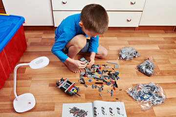 Little boy collects plastic constructor