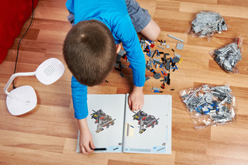 Little boy collects children's plastic building kit