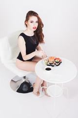Young woman eating sushi at Japanese restaurant