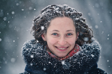 Beauty girl winter portrait with flying snowflakes