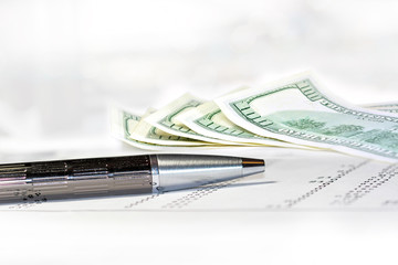 Ballpoint pen on financial statements with us dollars.
