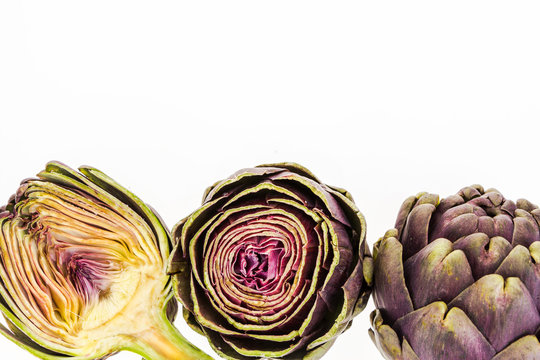 Three fresh purple artichokes,  on white background with copy-space