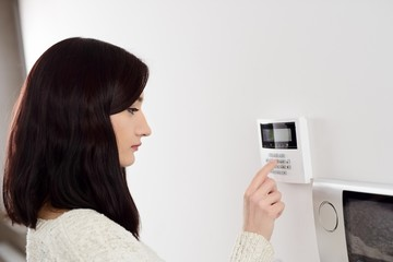 woman entering code on keypad of home security alarm Wall mural