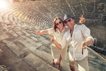 Positive young couple take selfie photo in Side antique amphithe