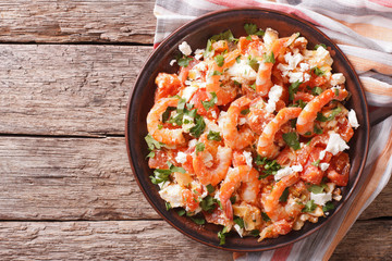 Shrimp saganaki with tomato and feta cheese on a plate. Horizontal top view
