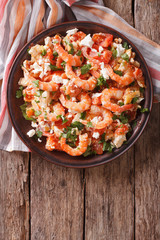Shrimp saganaki with tomato and feta cheese on a plate. vertical top view