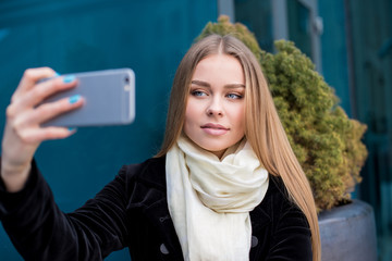 Young woman taking selfie on the street