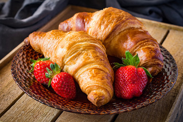 Two croissants and fresh strawberries on brown plate on rustic wooden background. Freshly baked french pastry and berries for breakfast