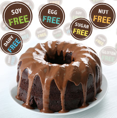 Ring chocolate cake with glaze on plate and signs with text closeup