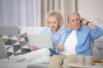 Mature couple using laptop and mobile phone at home