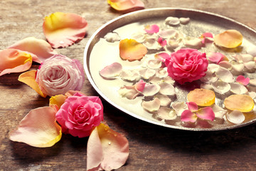 Pink and yellow rose petals in silver bowl with water on wooden background