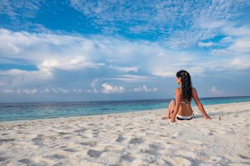 Girl walking along a tropical beach in the Maldives.