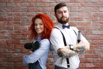 Two professional hairdresser on brick wall background
