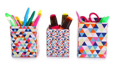 Three bright holders full of office supplies isolated on white background