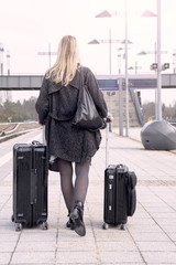 woman walking with suitcases at train station