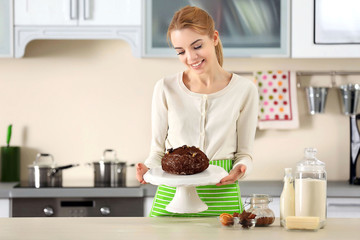 Young woman serving a chocolate cake